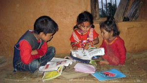 Three children reading a book together in a village in Nepal, April 2011. Photo by Nirmal Dulal via wikicommons