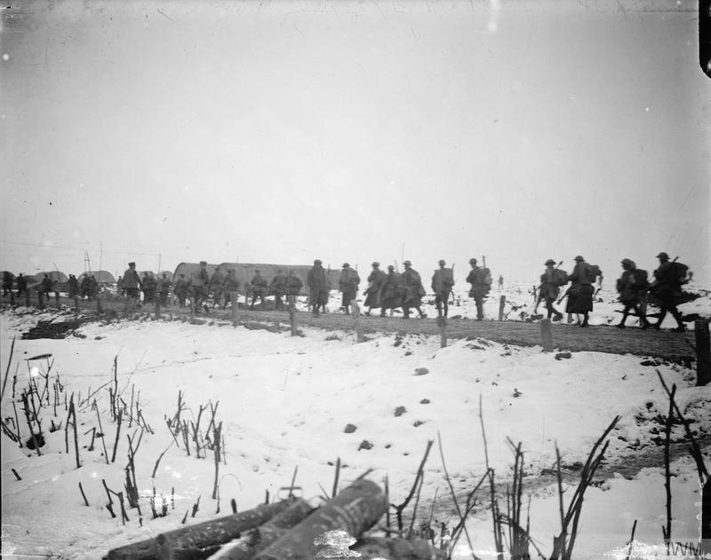 The British Army on the Western Front, 1914-1918. Troops going up to the trenches through the snow along a road in single file, La Boisselle, February 1917. By Lt John Warwick. From the Imperial War Museum collection via wikicommons.